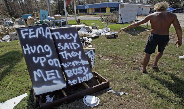 Carpenter Alan Perkins walks past a sign put up by another resident living in a tented city in Bay St. Louis, Miss., Thursday, Sept. 8 , 2005. The victim of Hurricane Katrina put up the sign after she called four times for FEMA's assistance and was always prompted to leave a message. The sign reads,